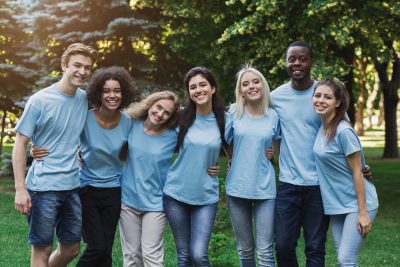 group of happy young adult volunteers embracing at park